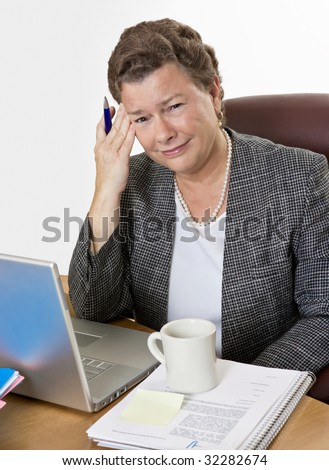 Mature businesswoman at her desk having a hot flash and a headache, looking at camera, very distressed. - stock photo