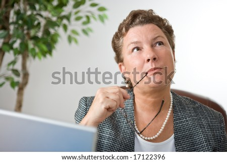 Mature businesswoman at her laptop, gazing into space and thinking. - stock photo