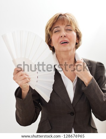 Mature businesswoman cooling herself with a fan. - stock photo