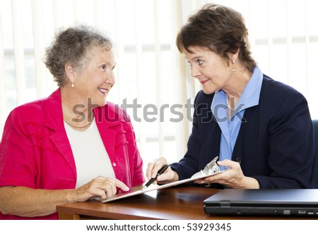 Mature businesswoman discusses a contract with her senior client.  Could also be sales related. - stock photo