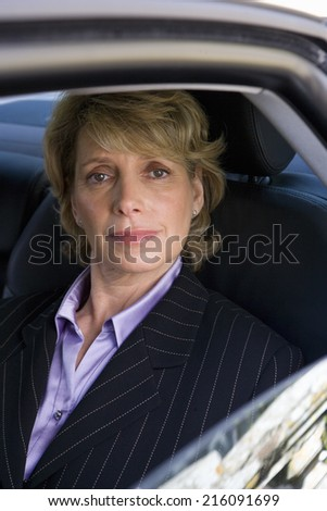 Mature businesswoman in back of car, smiling, portrait - stock photo