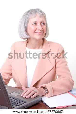 Mature businesswoman in office wearing peach jacket. There are several others in this series.