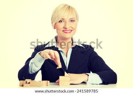 Mature businesswoman's sitting behind the table with blocks.