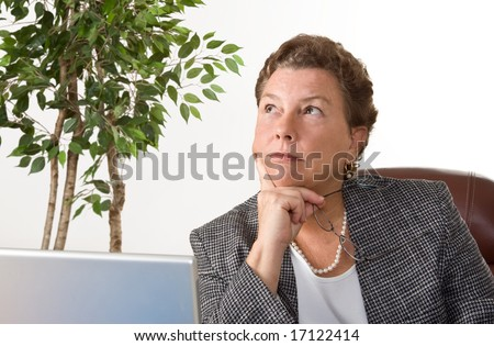 Mature businesswoman sitting at laptop in her office, pondering a decision. - stock photo