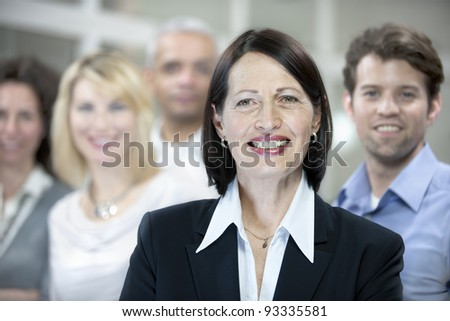 mature businesswoman with colleagues at the back - stock photo
