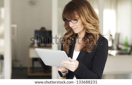 Mature Businesswoman with Digital Tablet in Office - stock photo