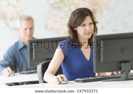 Mature businesswoman working on computer with colleague in background at office