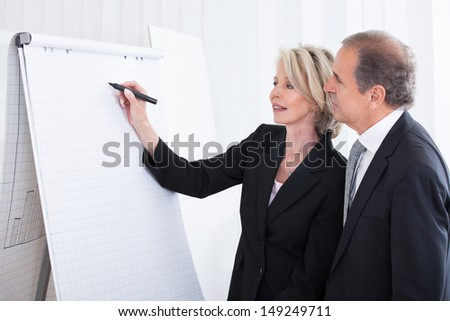 Mature Businesswoman Writing On Flipchart While Male Coworker Looking At It In Office - stock photo
