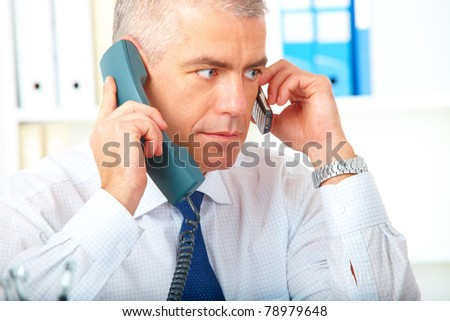 Mature busy  businessman with two phones working in office - stock photo
