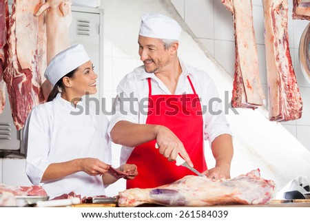 Mature butchers looking at each other while working together at counter in butchery - stock photo