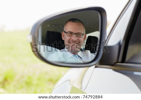 mature caucasian business man looking at camera through rear view mirror. Horizontal shape, head and shoulders