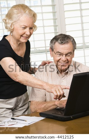 Mature Caucasian couple looking at laptop.