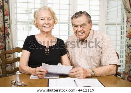 Mature Caucasian couple looking at their bills.