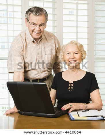 Mature Caucasian couple looking at their calendar and using laptop.