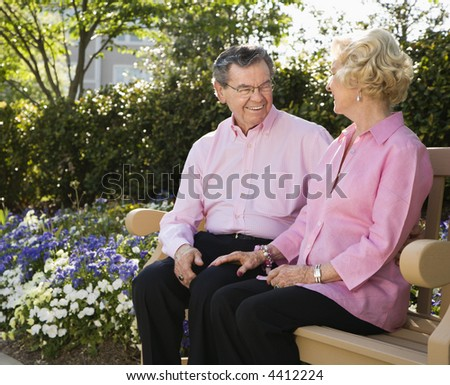 Mature Caucasian couple sitting on bench looking at each other.
