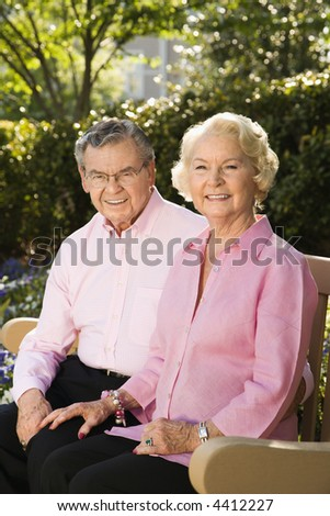 Mature Caucasian couple sitting on bench looking at viewer.
