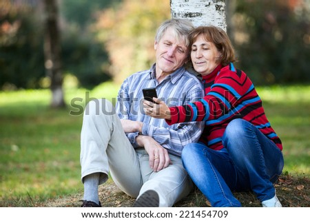 Mature Caucasian couple sitting together and making selfie with cellphone in park - stock photo