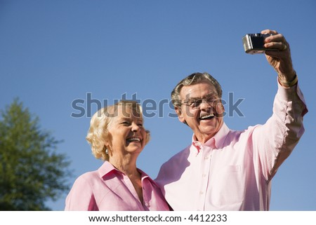 Mature Caucasian couple taking picture of themselves.