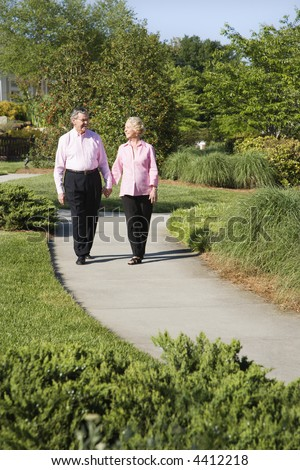 Mature Caucasian couple walking down sidewalk.