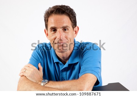 Mature Caucasian male sitting with his forearms on a table, and a thoughtful expression for the camera