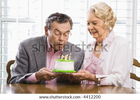 Mature Caucasian man blowing candles out on birthday cake while Mature Caucasian woman watches.