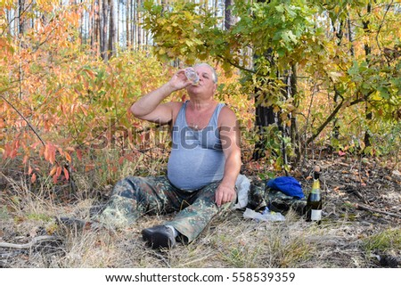 Mature caucasian man drinking water in the forest