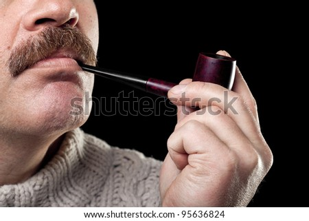 mature caucasian man holding smoking pipe in hand isolated on black background - stock photo