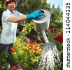 Mature caucasian man watering green garden with a lot of flowers - stock photo