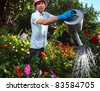 Mature caucasian smiling man watering her garden with a lot of flowers - stock photo