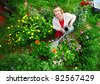 Mature caucasian smiling woman watering her garden with a lot of flowers - stock photo
