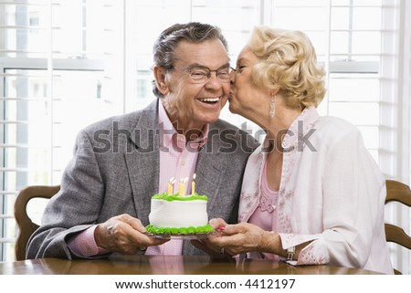 Mature Caucasian woman kissing mature Caucasian man while holding birthday cake.
