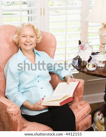 Mature Caucasian woman sitting in chair reading a book.
