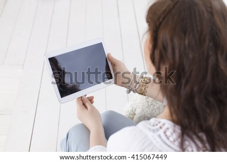 Mature caucasian woman with a tablet, sitting in armchair. View from above. Horizontal color image. Light background - stock photo