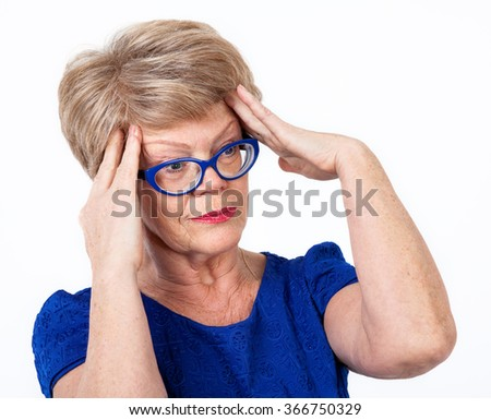 Mature Caucasian woman with migraine, holding her head with hands, white background - stock photo