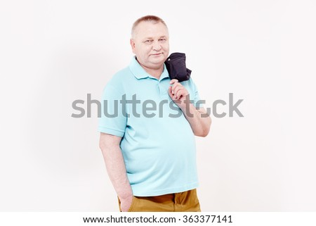 Mature cheerful man wearing blue shirt and brown trousers standing with hand in pocket, holding blue jacket over his shoulder and smiling against white wall - happy retirement concept