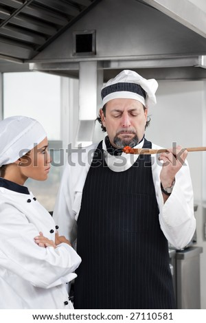 mature chef holding wooden spool and tasting tomato sauce. - stock photo