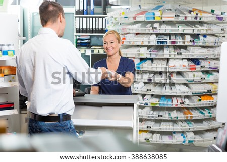 Mature Chemist Giving Product To Customer In Pharmacy - stock photo