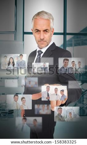 Mature classy businessman using futuristic interface showing partners - stock photo