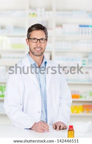 Mature confident male pharmacist at pharmacy counter - stock photo