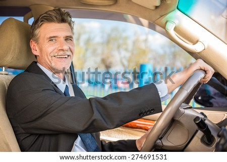 Mature confident smiling businessman  in suit driving his luxurious car. - stock photo