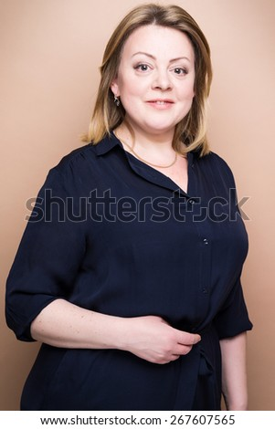 mature confident woman studio shot on brown background - stock photo