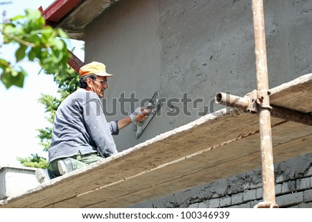Mature contractor plasterer working outdoors.  Construction Site. Work Tool.