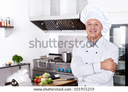 Mature cook in the kitchen - stock photo