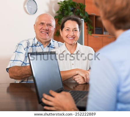 Mature couple answer questions of agent with notebook in  office - stock photo
