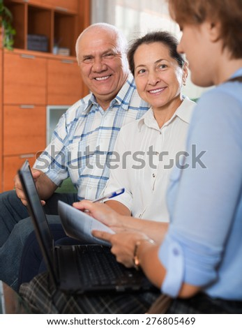 Mature couple answer questions of caseworker with computer in office - stock photo