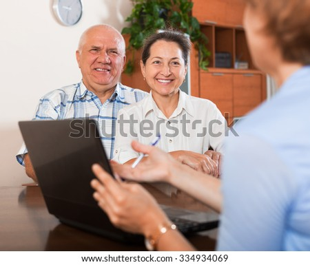 Mature couple answer questions of caseworker with laptop in home  - stock photo