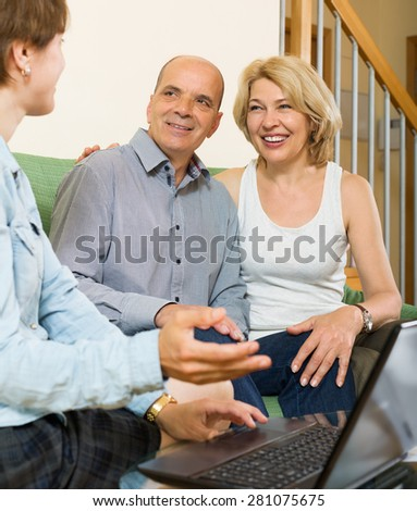 Mature couple answer questions of social worker at home