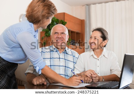 Mature couple answer questions of social worker with notebook in  office - stock photo