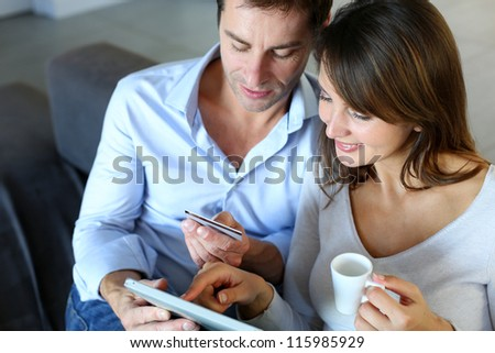 Mature couple at home using credit card to shop online - stock photo