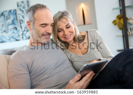 Mature couple at home websurfing with tablet - stock photo